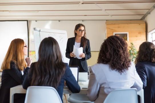 businesswomen-looking-speaker-with-papers