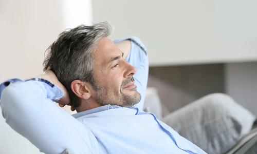 Middle-aged man having a restful moment relaxing on sofa (500x300)